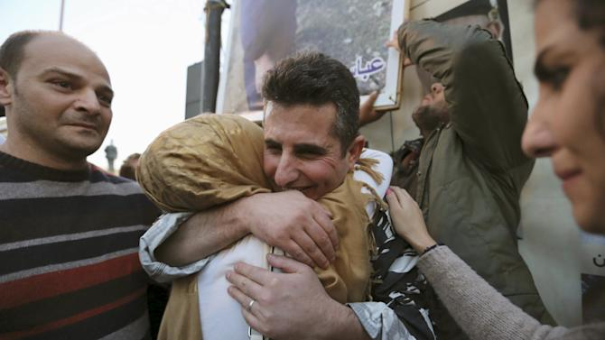 A newly released policeman, who was captured by the al Qaeda-linked Nusra Front in Arsal, embraces his relative during a celebration outside the government palace in downtown Beirut