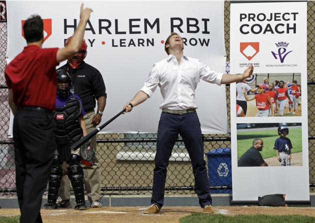 Britain's Prince Harry reacts after hitting a baseball pitched to him by New York Yankees' Mark Teixeira, left, during a visit to the Harlem RBI youth sports and school program in New York, Tuesday, M