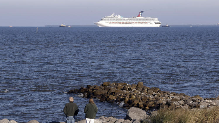 People watch the cruise ship Carnival Triumph as it is towed into Mobile Bay from Dauphin Island, Ala., Thursday, Feb. 14, 2013. The ship with more than 4,200 passengers and crew members has been idled for nearly a week in the Gulf of Mexico following an engine room fire. (AP Photo/Dave Martin)