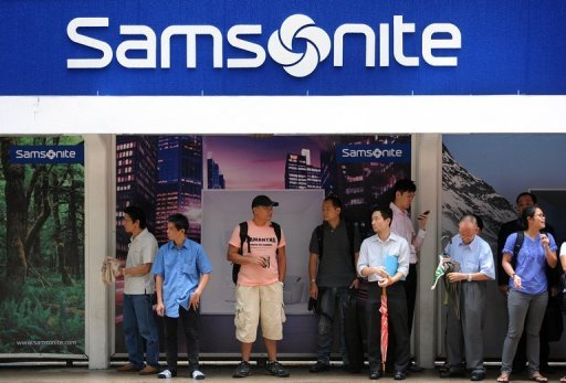 <p>Photo illustration shows people waiting at a tram stop next to Samsonite advertising in Hong Kong. Samsonite said Monday it had withdrawn some of its suitcases from Hong Kong stores after a consumer group found they contained high levels of chemicals that may cause cancer.</p>