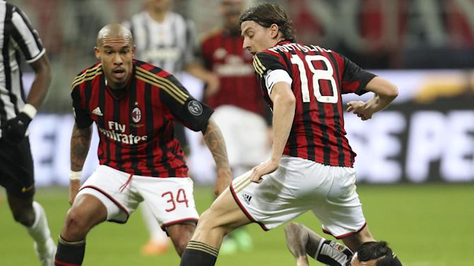 Juventus forward Carlos Tevez, bottom, of Argentina, challenges for the ball with AC Milan midfielders Riccardo Montolivo, top right, and Nigel de Jong, of the Netherlands, during the Serie A soccer match between AC Milan and Juventus at the San Siro stadium in Milan, Italy, Sunday, March 2, 2014