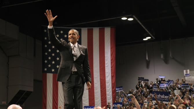 President Barack Obama waves as he arrives for a rally for Washington Gubernatorial candidate John Kitzhaber, left, at the Oregon Convention Center in Portland, Ore., Wednesday, Oct.  20, 2010. (AP Photo/Susan Walsh)