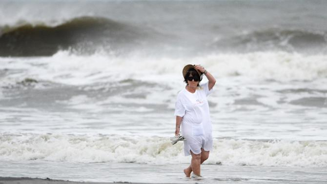 A beach goer holds on to her hat as she walks along a breezy Coligny Beach Park on Hilton Head Island, S.C., watching the waves generated by Hurricane Sandy near the time of high tide on Saturday morning, Oct. 27, 2012. Hurricane Sandy _ upgraded again Saturday just hours after forecasters said it had weakened to a tropical storm _ was barreling north from the Caribbean and was expected to make landfall early Tuesday near the Delaware coast, then hit two winter weather systems as it moves inland, creating a hybrid monster storm. (AP Photo/The Island Packet, Jay Karr)