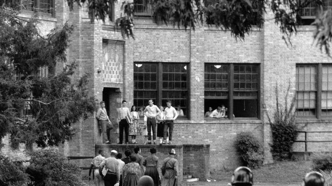 FILE  - In this  Oct. 15, 1957 file photo, seven of nine black students walk onto the campus of Central High School in Little Rock, Ark., with a National Guard officer as an escort as other troops watch. More than a half-century after federal troops escorted nine black students into an all-white school, efforts to desegregate Little Rock's classrooms are at another turning point.  The state wants to end its long-running payments for desegregation programs, but three school districts that receive the money say they need it to continue key programs. And a federal judge has accused the schools of delaying desegregation so they can keep receiving an annual infusion of $70 million. (AP Photo, Fred Kaufman, File)