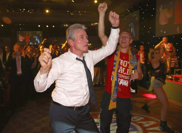 Bayern Munich coach Jupp Heynckes dances together with midfielder Bastian Schweinsteiger at the team's banquet in London