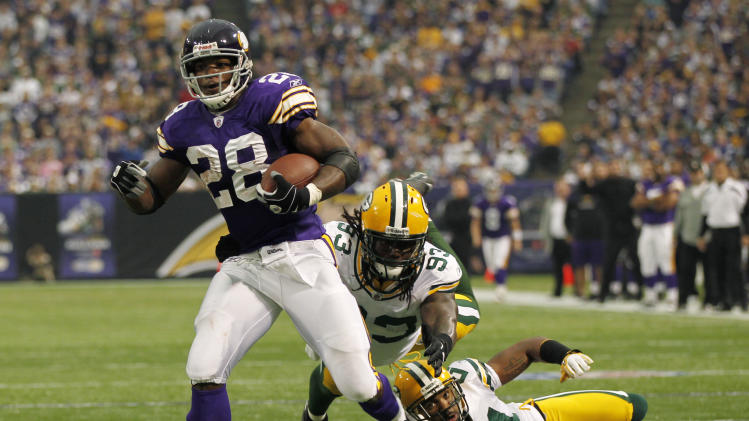 Minnesota Vikings running back Adrian Peterson (28) breaks a tackle by Green Bay Packers linebacker Erik Walden (93) and cornerback Charles Woodson (21) during the first half of an NFL football game Sunday, Oct. 23, 2011, in Minneapolis. (AP Photo/Andy King)