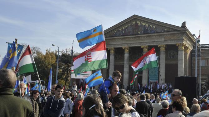 Participants of a march for Szekler autonomy, organized in support of the Great March of the Szeklers in central Romania's Szekler Land, gather at Heroes Square, in Budapest, Hungary carrying Hungarian and Szekler flags, on Sunday, Oct. 27, 2013. Szeklers are ethnic Hungarians living in the eastern part of Transylvania, Romania. The Great March of the Szeklers was organized by the Szekler National Council of Romania on the same day. (AP Photo/MTI,Attila Kovacs)