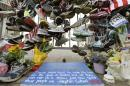 In this April 25, 2013 photo, running shoes and other items adorn a makeshift memorial near the Boston Marathon finish line in Boston's Copley Square. Thousands of items from the original memorial for marathon bombing victims are going on display at the Boston Public Library in April 2014 to mark the anniversary of the attacks. (AP Photo/Elise Amendola)