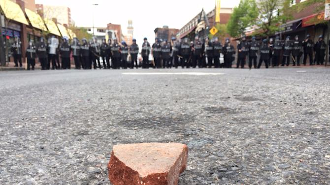 A brick rests on the ground in front of members of the Baltimore Police Department, Monday, April 27, 2015, during unrest following the funeral of Freddie Gray in Baltimore. (Karl Merton Ferron/The Baltimore Sun via AP)