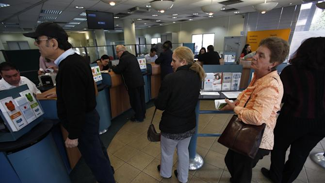 People are served in a branch of Bank of Cyprus in Nicosia, Thursday, March 28, 2013. Banks in Cyprus reopened to customers for the first time in nearly two weeks Thursday, albeit with strict restrictions on transactions, after being closed to prevent people withdrawing all their savings during the country's acute financial crisis. Large lines had formed outside the banks ahead of the opening of banks for six hours from noon. (AP Photo/Petros Karadjias)