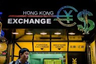 A man looks on in front of a currency exchange booth in Hong Kong on October 22. The Hong Kong dollar continued to sit at the high end of its trading range against the US dollar despite an intervention late last week by the city's de facto central bank to weaken the unit