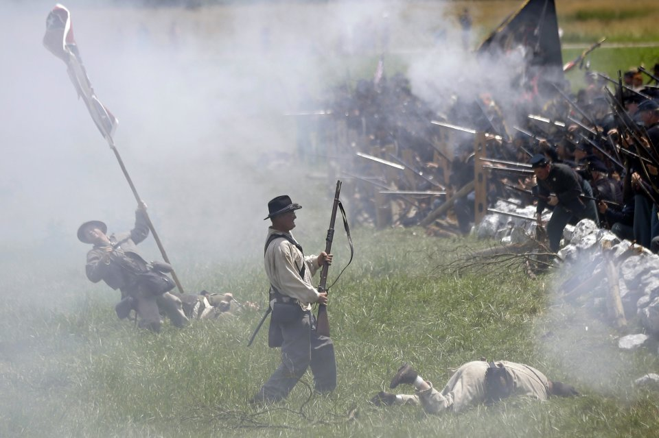 "In this June 30, 2013 file photo, re-enactors portray Pickett's Charge during ongoing activities commemorating the 150th anniversary of the Battle of Gettysburg at Bushey Farm in Gettysburg, Pa. One of the most difficult challenges for any mock general at a Civil War battle re-enactment is deciding which of his men must ""die."" (AP Photo/Matt Rourke)"