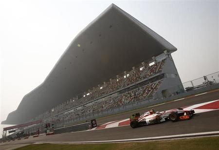 HRT Formula One driver Narain Karthikeyan of India drives out of the pit lane during the first practice session of the Indian F1 Grand Prix at the Buddh International Circuit in Greater Noida, on the