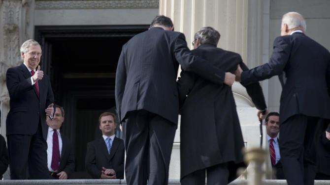 Senate Minority Leader Sen. Mitch McConnell of Ky. gives a thumbs-up at left, as Sen. Mark Kirk, R-Ill., second from right, accompanied by Vice President Joe Biden, right, and Sen. Joe Manchin, D-W.Va., walks up the steps to the Senate door of the Capitol building, Thursday, Jan. 3, 2013, on Capitol Hill in Washington. Kirk said he often visualized climbing the 45 steps of the U.S. Capitol as a source of inspiration during his months of grueling physical therapy after suffering a major stroke last year.     (AP Photo/ Evan Vucci)