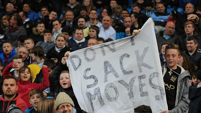 Manchester City supporters display a banner with reference to Manchester United manager David Moyes, during the English Premier League soccer match between Manchester City and West Bromwich at the Etihad Stadium,  Manchester, England, Monday, April  21, 2014