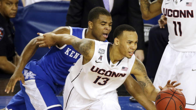Connecticut guard Shabazz Napier (13) tries to control the ball as Kentucky guard Aaron Harrison (2) defends during the second half of the NCAA Final Four tournament college basketball championship game Monday, April 7, 2014, in Arlington, Texas. (AP Photo/Tony Gutierrez)