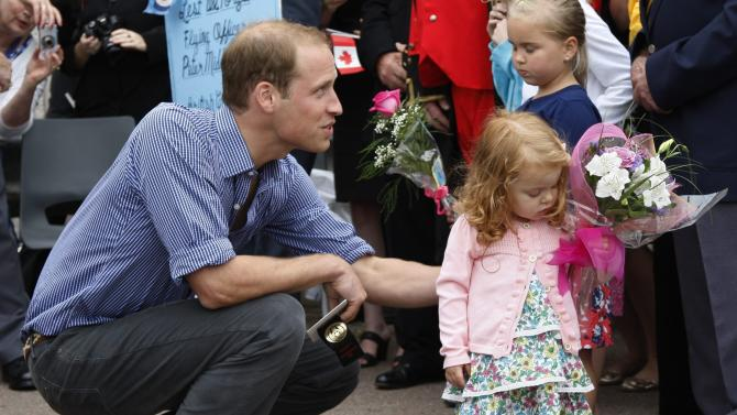 Prince William, the Duke of Cambridge, greets two-year-old Alexa Currie, who is reluctant to give up her flowers, in Summerside,  P.E.I. Monday, July 4, 2011. (AP Photo/The Canadian  Press, Ryan Remiorz)