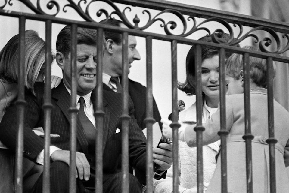 FILE - In this Nov. 13, 1963 file photo, U.S. President John F. Kennedy and first lady Jacqueline Kennedy sit with their children, John Jr. and Caroline, on a portico overlooking the White House South Lawn in Washington. In background is British Ambassador David Ormsby Gore. (AP Photo)