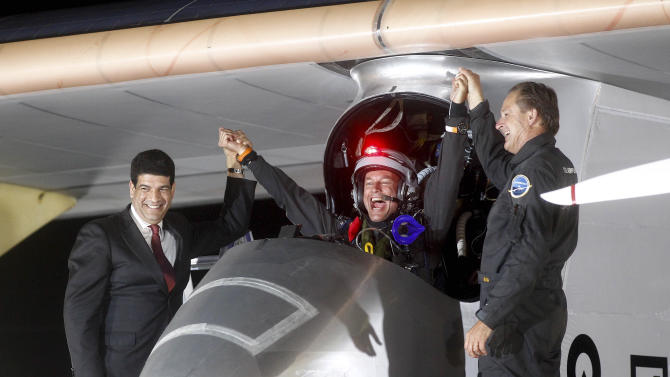 Solar Impulse pilots Bertrand Piccard, center, celebrates with Andre Borschberg, right, and Mustapha Bakkoury, president of the Moroccan Agency for Solar Energy upon arrival at Rabat airport, Morocco, Tuesday, June 5, 2012. The experimental solar-powered airplane landed in Morocco's capital late Tuesday after a 20-hour trip from Madrid in the first transcontinental flight by a craft of its type. The mission is being described as a final dress rehearsal for a round-the-world flight with a new and improved plane in 2014. (AP Photo/Abdeljalil Bounhar)
