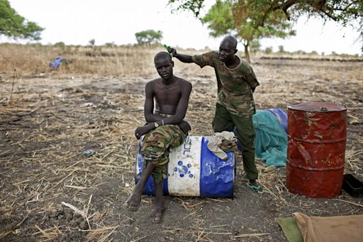 A Sudan People's Liberation Movement Army (SPLA) solider has his hair cut at a frontline position in Pana Kuach, Unity State, South Sudan on Friday, May 11, 2012. In late April, tensions between Sudan and South Sudan erupted&lt;br /&gt;&lt;br /&gt;&lt;br /&gt;&lt;br /&gt;&lt;br /&gt;&lt;br /&gt;&lt;br /&gt;&lt;br /&gt;&lt;br /&gt;<br />  into armed conflict along their poorly defined border. Thousands of SPLA forces have been deployed to Unity State where the two armies are at a tense stalemate around the state's expansive oil fields. Fighting between the armies lulled in early May after the U.N. Security Council ordered the countries to resume negotiations. South Sudan seceded from the Republic of Sudan in July 2011 following decades of civil war. (AP Photo/Pete Muller)