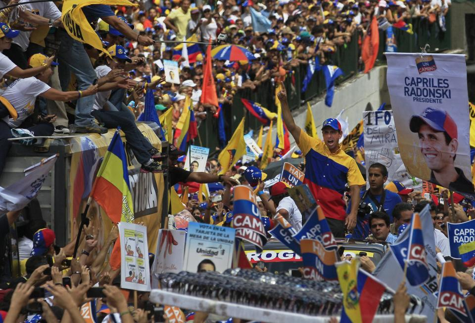 ALTERNATIVE CROP OF XFLL104 - Opposition presidential candidate Henrique Capriles, center, gestures to supporters during a campaign rally in Caracas, Venezuela, Sunday, Sept. 30, 2012. Presidential elections in Venezuela are scheduled for Oct. 7. (AP Photo/Fernando LLano)