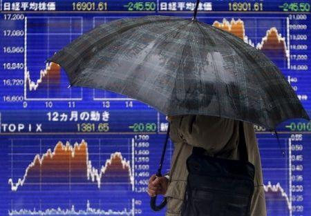 A pedestrian holding an umbrella walks past an electronic board showing the graphs of the recent fluctuations of Japan's Nikkei average outside a brokerage in Tokyo