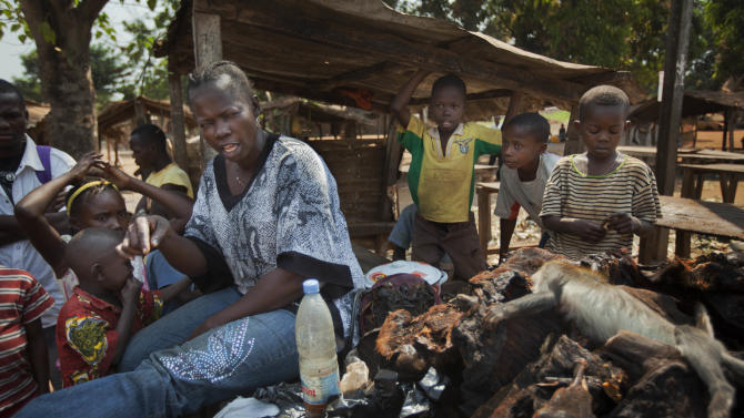 A bushmeat seller, left, who declined to give her name, talks about how she and others in her neighborhood plan to remain there despite the increasingly fraught situation, as she sits by her wares at the market in the Bimbo neighborhood of the capital Bangui, Central African Republic, Tuesday, Jan. 1, 2013. President Francois Bozize's government is coming under growing threat as rebels vowing to overthrow him rejected appeals from the African Union to hold their advance and try to form a coalition government. (AP Photo/Ben Curtis)