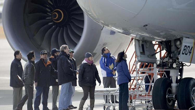U.S. officials, center,  inspect a All Nippon Airways jet which made an emergency landing Wednesday, at Takamatsu airport in Takamatsu, western Japan, Friday, Jan. 18, 2013. An official with Japan's transport safety board says four U.S. officials, including two Boeing Co. representatives, have arrived at the airport in western Japan to inspect the troubled Boeing 787 jet. (AP Photo/Kyodo News)  JAPAN OUT, MANDATORY CREDIT, NO LICENSING IN CHINA, HONG KONG, JAPAN, SOUTH KOREA AND FRANCE