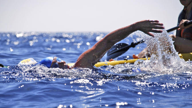 In this photo provided by Diana Nyad via the Florida Keys News Bureau, endurance swimmer Diana Nyad swims in the Florida Straits between Cuba and the Florida Keys Monday, Aug. 20, 2012. After being delayed by a weather squall line late Sunday night and early Monday morning, her team reported that Nyad was back on course in her effort to be the first swimmer to transit the Florida Straits from Cuba to the Keys without a shark cage. (AP Photo/Diana Nyad via the Florida Keys News Bureau, Christi Barli)