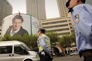 "A policeman (C) and security guard stand near a giant poster of Roger Federer in Shanghai on October 5. Security precautions are in place for Federer and his family in the Chinese city, after a unknown blogger made the outlandish threat to ""assassinate"" the 17-time Grand Slam champion"