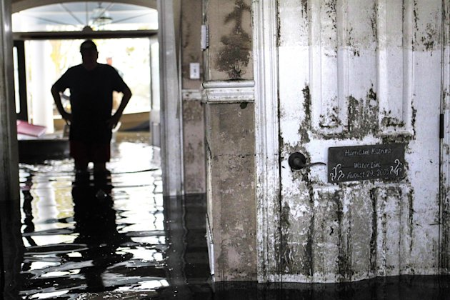 Don Duplantier walks through his flooded home as water recedes from Hurricane Isaac in Braithwaite, La., Sunday, Sept. 2, 2012. In the foreground is a sign marking the waterline from Hurricane Katrina
