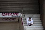 An Indian resident rests his head in his hands in front of closed shops at Lajpat Nagar market in New Delhi early September 20. India's retail market clocks $500 billion in sales annually, a figure expected to grow to $800 billion in the next five years, Technopak says. Of that, chain stores account for $33 billion, a sum seen growing to $80 billion within five years