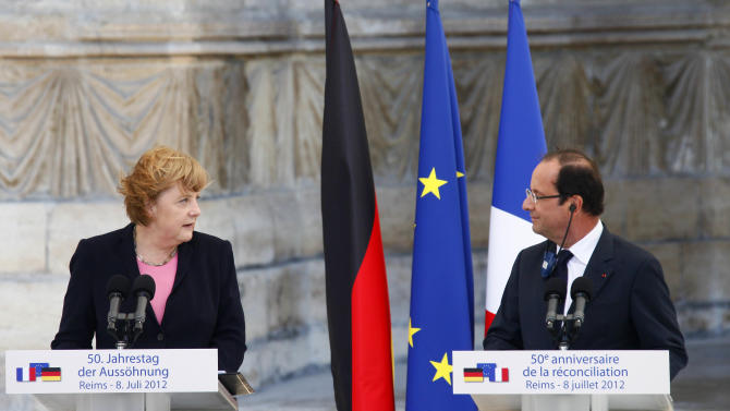 German Chancellor Angela Merkel, and French President Francois Hollande look at each other during a speech in front of the Reims cathedral in Reims, eastern France, Sunday July 8, 2012. Leaders of France and Germany meet to mark 50 years of an important step toward cooperation after two world wars, amid today's tensions over Europe's financial crisis. (AP Photo/Michel Spingler)