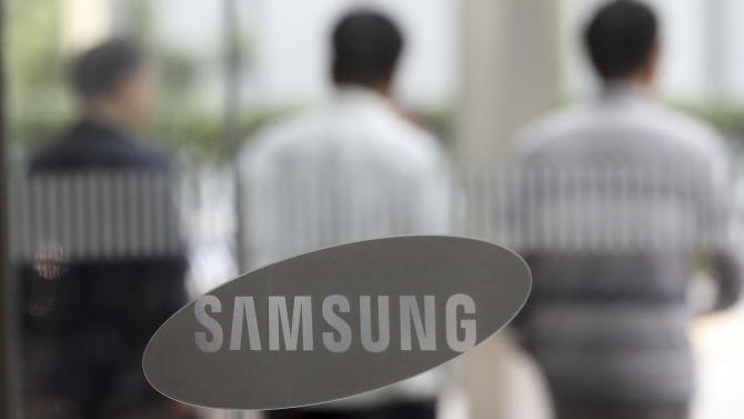 People walk by the logo of Samsung Electronics Co. near its office in Seoul, South Korea, Wednesday, Oct. 7, 2015. Samsung Electronics announced a forecast-beating profit for the third quarter Wednesday, sending its share price up more than 7 percent, but analysts said strong component sales and favorable currency exchange rates masked persistent weakness in its smartphone business. (Choi jae-gu/Yonhap via AP) KOREA OUT