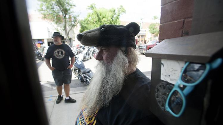"""Bear"" Adams, of Daytona Beach, Fla., waits to card patrons of The Dungeon Bar, days before the official kickoff of the 74th Annual Sturgis Motorcycle Rally in Sturgis, S.D, on Friday, August 1, 2014. Organizers expect attendance at this week's Sturgis Motorcycle Rally to top the estimated 466,000 who made the annual trek last year. (AP Photo/Toby Brusseau)"