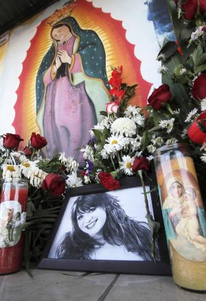 Photos and flowers honoring late singer Jenni Rivera, placed by fans next to religious images, are seen at the cemetery where her mother is buried in Hermosillo, northern Mexico, Monday, Dec. 10, 2012. U.S. authorities confirmed Monday that Rivera, a U.S.-born singer whose soulful voice and openness about her personal troubles made her a Mexican-American superstar, was killed in a plane crash early Sunday in northern Mexico. (AP Photo/Baldemar De Los Llanos)