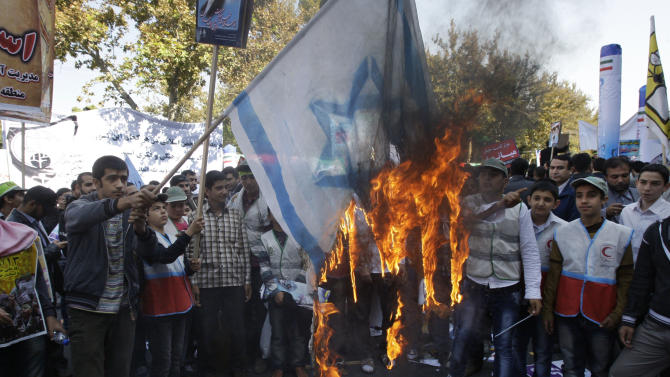 Iranians burn a representation of an Israeli flag during an annual state-backed rally outside the former U.S. Embassy in Tehran, Iran, Friday, Nov. 2, 2012. The rally marks the Nov. 4, 1979, storming of the building by militant students who held 52 Americans hostage for 444 days to protest U.S. failure to hand over the toppled shah Mohammad Reza Pahlavi to Iran for trial. Gen. Mohammad Reza Naqdi of the powerful Revolutionary Guard, not shown, addressed the rally saying the U.S. must annul the CIA, pull out its warships from the Persian Gulf and dismantle its military bases from 50 countries around the world if it wants to restore ties with Tehran. (AP Photo/Vahid Salemi)