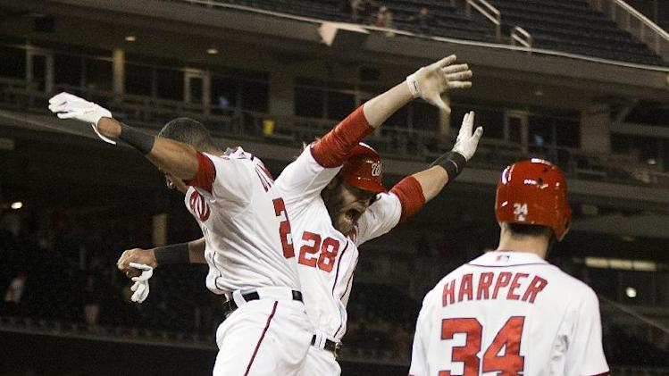Washington Nationals Jayson Werth (28) celebrates scoring the wining run, with teammates Ian Desmond (20) and Bryce Harper (34), on a single hit by Adam LaRoche during the ninth inning of a baseball game against the Los Angeles Angels, Wednesday, April 23, 2014 in Washington. The Nationals won 5-4