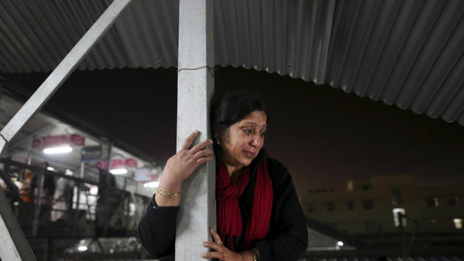 An Indian woman weeps as she watches from a staircase as rescue workers tend to the bodies of those killed in a stampede on a railway platform at the main railway station in Allahabad, India, Sunday, Feb. 10, 2013. At least ten Hindu pilgrims attending the Kumbh Mela were killed and more then thirty were injured in a stampede on an overcrowded staircase, according to Railway Ministry sources.  (AP Photo/Kevin Frayer)