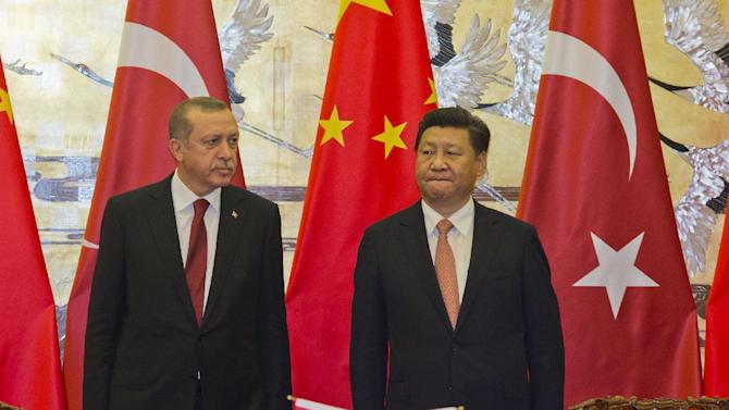 Turkey's President Recep Tayyip Erdogan, left, stands with Chinese President Xi Jinping during a signing ceremony at the Great Hall of the People in Beijing, Wednesday, July 29, 2015. Erdogan met with top Chinese officials Wednesday amid tensions over China's treatment of its Uighur minority and sensitive negotiations surrounding the possible purchase of a Chinese missile system. (AP Photo/Ng Han Guan, Pool)