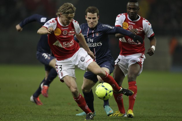 Franck Signorino and Bocundji Ca of Stade Reims fight for the ball with Kevin Gameiro of Paris St Germain during their French Ligue 1 soccer match in Reims