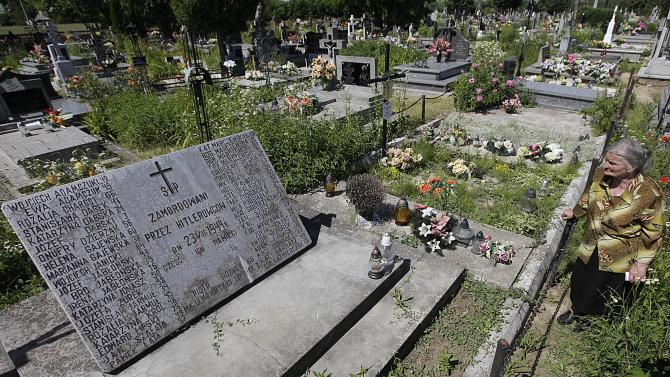 A mass grave and a monument in the village of Chlaniow, Poland, photographed on Wednesday, June 19, 2013, and holding the bodies of Poles killed in an attack on the village by the Nazi SS-led Ukrainian Self Defense Legion in 1944. Forty four villagers and one visitor were killed. An investigation by the AP revealed that a commander in the legion, Michael Karkoc, 94, is living in the United States. In his Ukrainian-language memoirs Karkoc said he was in Chlaniów at the time of the attack. None of the records uncovered by the AP links him directly to atrocities. (AP Photo/Czarek Sokolowski)