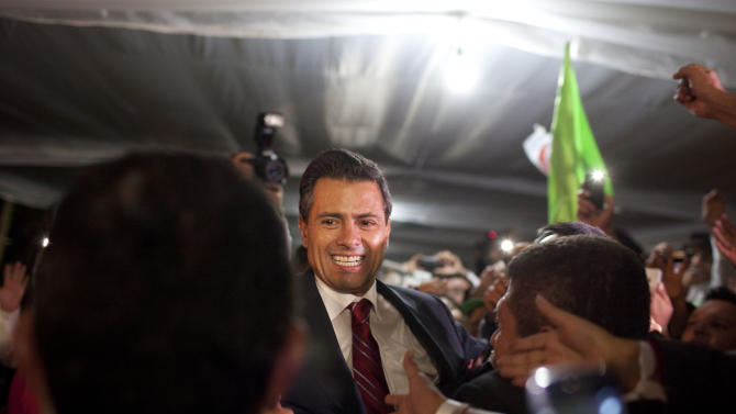 Enrique Pena Nieto, presidential candidate for the Revolutionary Institutional Party (PRI), greets supporters at his party's headquarters in Mexico City, early Monday, July 2, 2012. Mexico's old guard sailed back into power after a 12-year hiatus Sunday as the official preliminary vote count handed a victory to Pena Nieto, whose party was long accused of ruling the country through corruption and patronage. (AP Photo/Alexandre Meneghini)