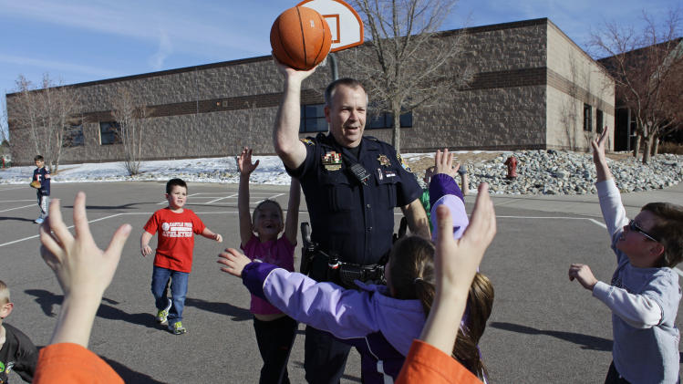 FILE - In this Thursday, Jan. 31, 2013 file photo, Douglas County Sheriff Department Lt. Brian Murphy plays with students on the playground during recess at Buffalo Ridge Elementary School, part of a new cooperative effort between law enforcement and schools for more routine police presence at local primary schools, in Castle Pines, Colo. Since the December school attack in Connecticut, county police have begun a practice of completing their paperwork from their cruisers in elementary school parking lots, and are encouraged to spend more time inside schools. (AP Photo/Brennan Linsley, File)