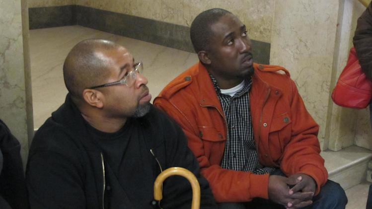 Mark Hedges, 45, left, of Cincinnati and Damon Robinson, 36, of Lexington, Ky., talk to their attorney inside the Hamilton County Court of Common Pleas, Monday, Nov. 5, 2012, in Cincinnati, shortly after filing a lawsuit against builders of Cincinnati's first and only casino, slated to open in the spring. The men were injured while pouring concrete on a second floor at the casino in January and allege that the construction firms neglected safety to get the project done on time. (AP Photo/Amanda Lee Myers)