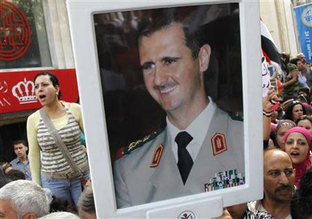 Supporters of Syrian President Bashar al-Assad's hold pictures of al-Assad during a rally at al-Sabaa Bahrat square in Damascus