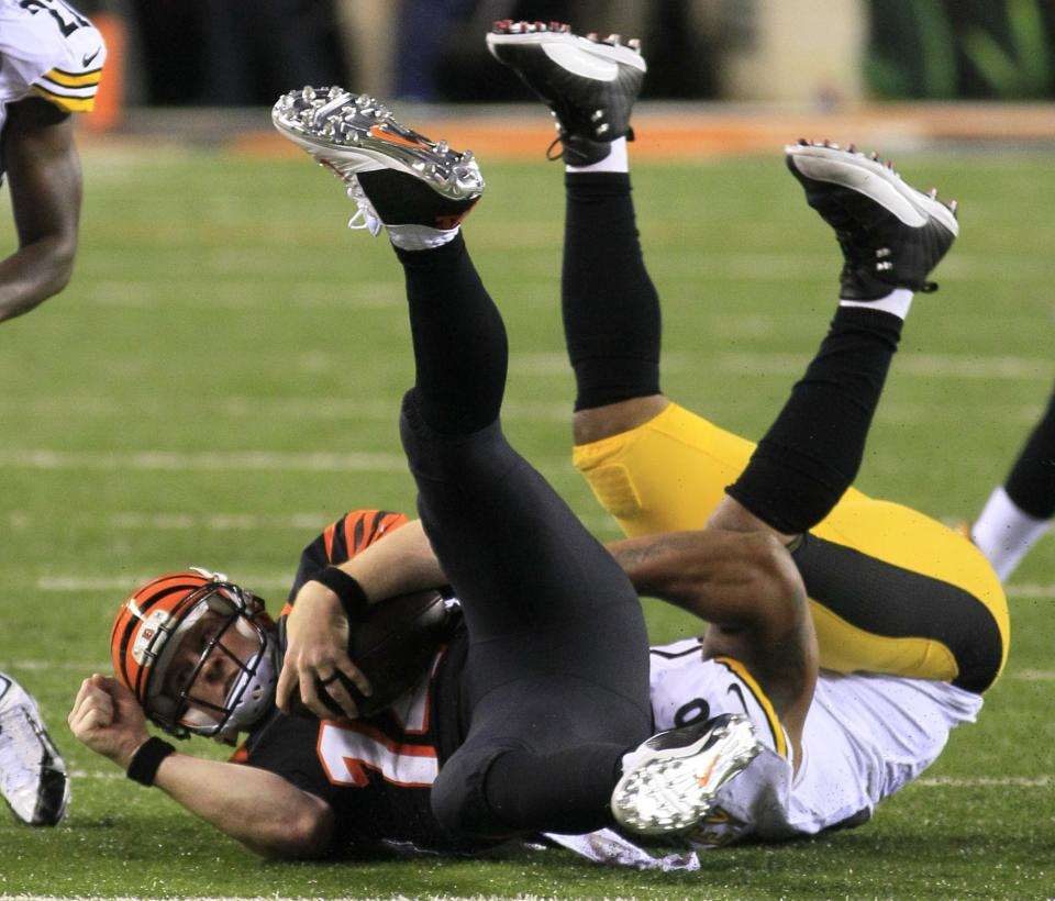 Cincinnati Bengals quarterback Andy Dalton, left, is tackled after a short gain by Pittsburgh Steelers outside linebacker LaMarr Woodley in the second half of an NFL football game, Monday, Sept. 16, 2013, in Cincinnati. (AP Photo/Tom Uhlman)
