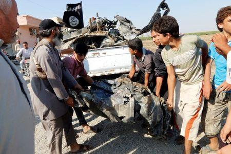 People carry a remnant of a war plane that crashed on the outskirts of Raqqa in northeast Syria