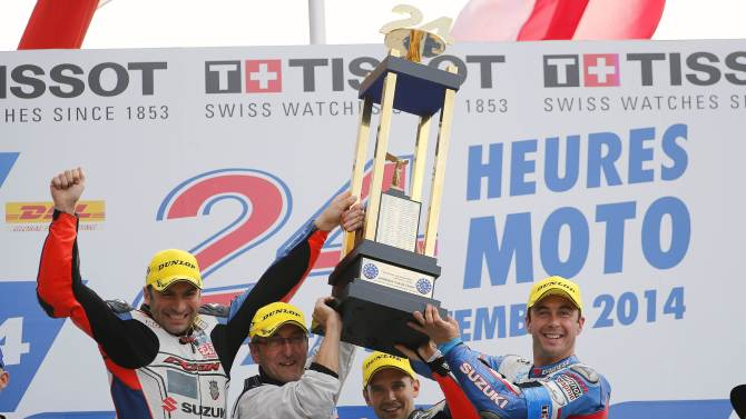 Suzuki riders Nigon, Delhalle and Philippe, all of France, hold the trophy with their team manager Meliand after their victory in the 37th Le Mans 24 Hours motorcycling endurance race in Le Mans