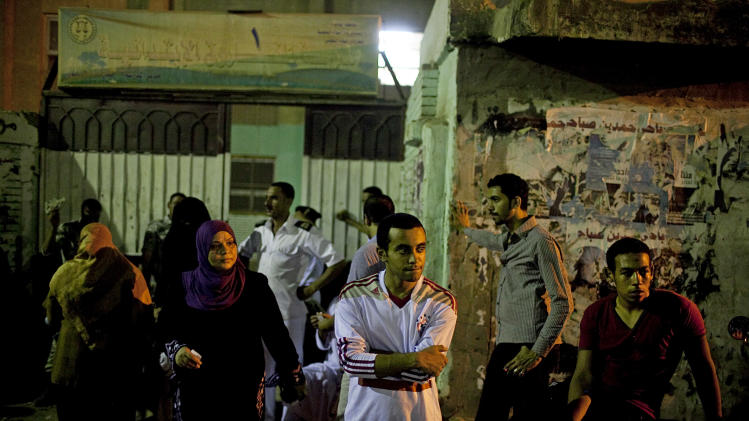 Egyptians stand outside a polling station in the Dar el- Salam neighborhood of Cairo, Egypt on Sunday, June 17, 2012. Shady Mohammed, 23, center, spoiled his ballot in protest of both of Egypt's remaining presidential candidates claiming that neither represented his sentiments. Egyptians continued a second day of voting into the night on Sunday in the country's landmark presidential runoff, choosing between Hosni Mubarak's ex-prime minister and an Islamist candidate from the Muslim Brotherhood after a race that has deeply polarized the nation. The two-day balloting will produce Egypt's first president since a popular uprising last year ousted Mubarak, who is now serving a life sentence.  (AP Photo/Pete Muller)